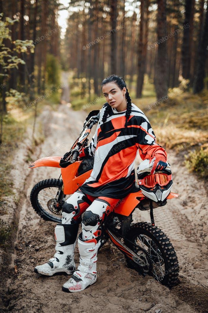 Hermosa mujer corredor sentado en su moto de motocross en un rastro de arena en el bosque