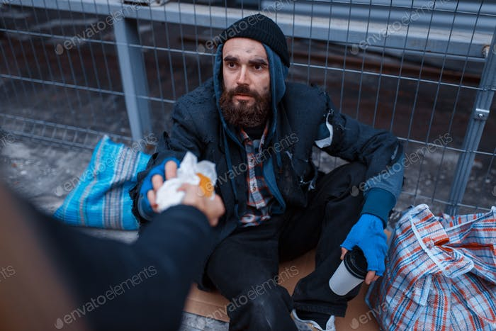 Male person gives food to bearded dirty beggar