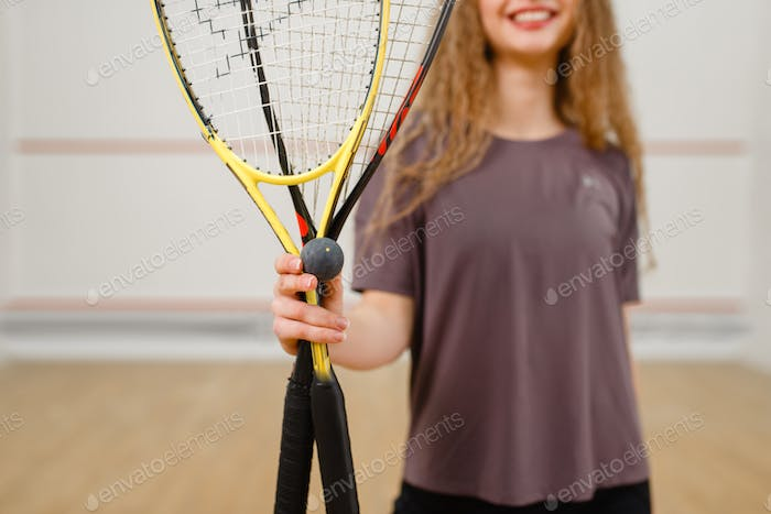 Female person shows squash racket and ball