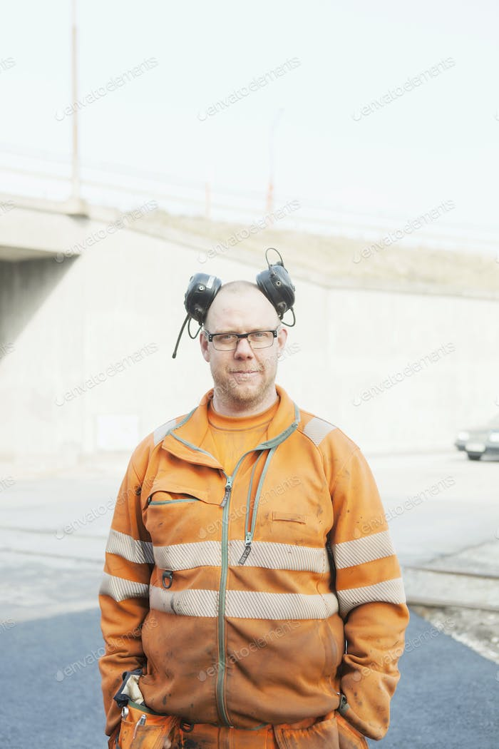 Portrait of confident manual worker at road construction site