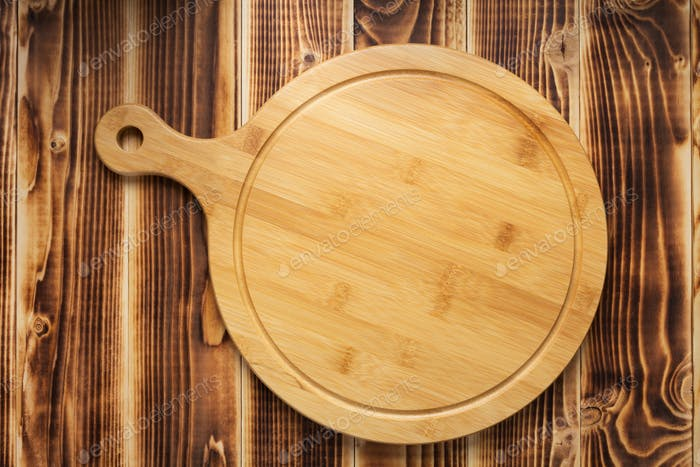 pizza cutting board at rustic wooden plank background