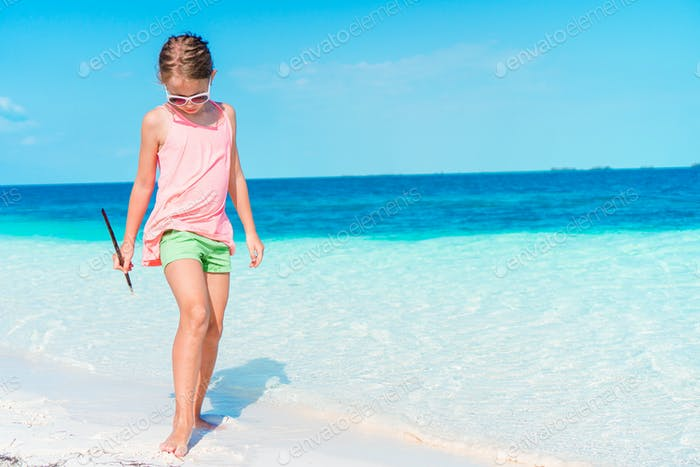 Beautiful little girl at beach having fun. Funny girl enjoy summer vacation