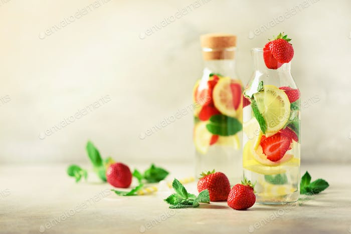 Strawberry detox water with mint, lemon on grey background. Citrus lemonade. Summer fruit infused