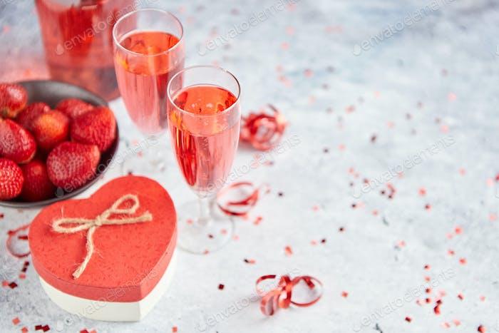 Flasche Roséchampagner, Gläser mit frischen Erdbeeren und herzförmiges Geschenk