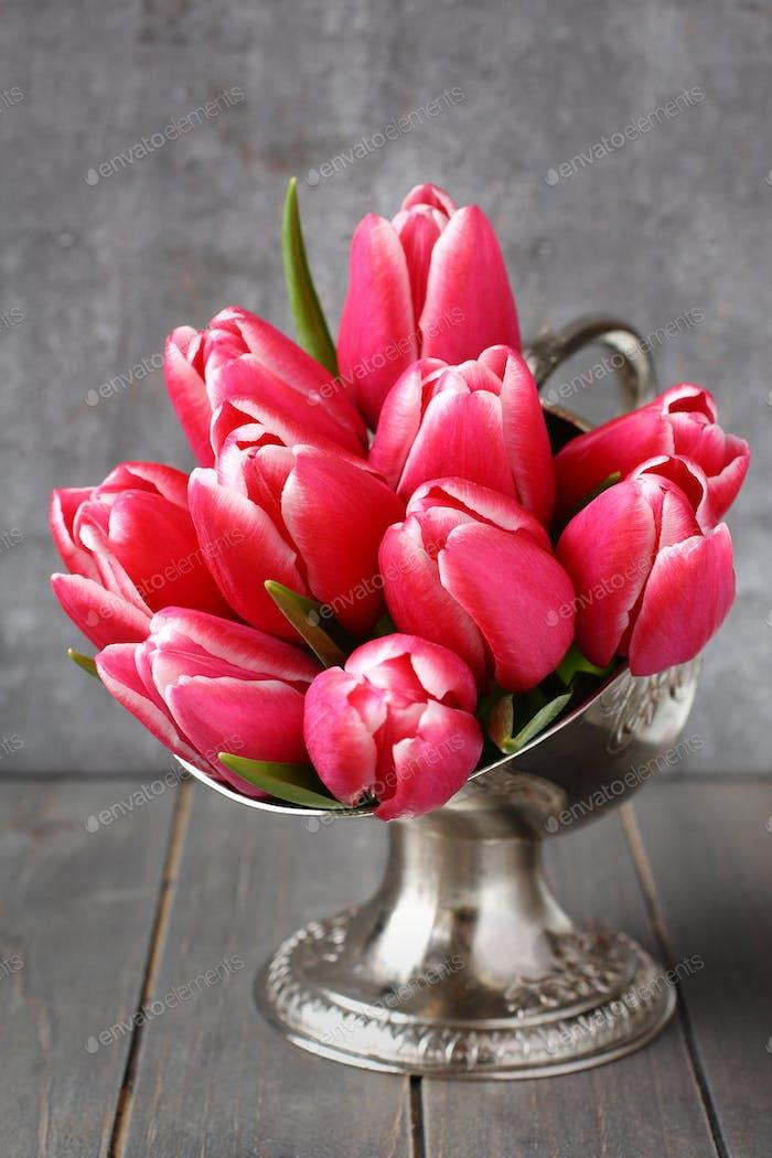 Blumenstrauß rosa Tulpen in Metallvase auf Holzhintergrund