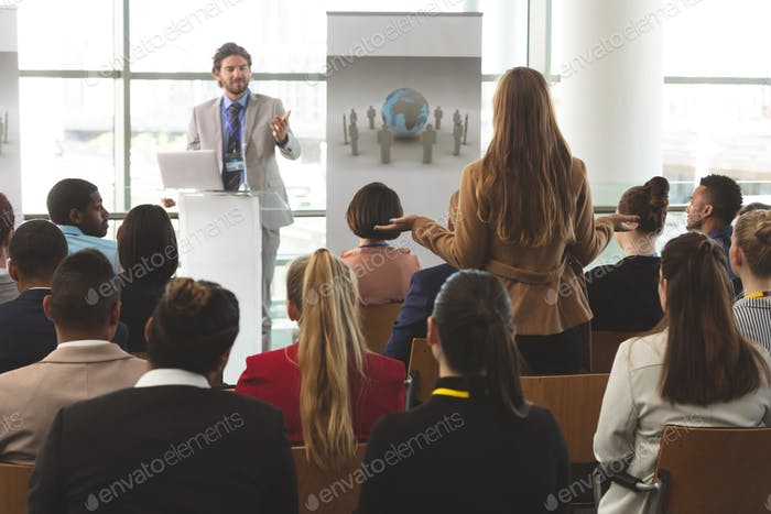 Businesswoman interacting with Caucasian businessman speaking at business seminar in office building