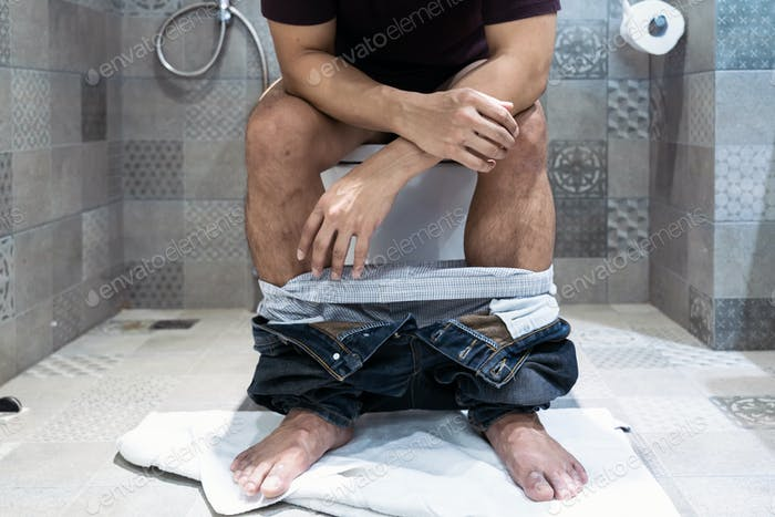 Man sitting on toilet bowl