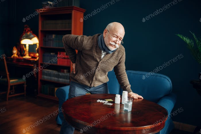 Sick elderly man holds his back in home office
