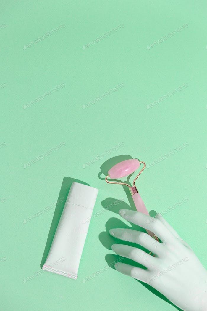 Face care concept art. Minimal still life design.  Massage quartz roller. Aqua menthe trends