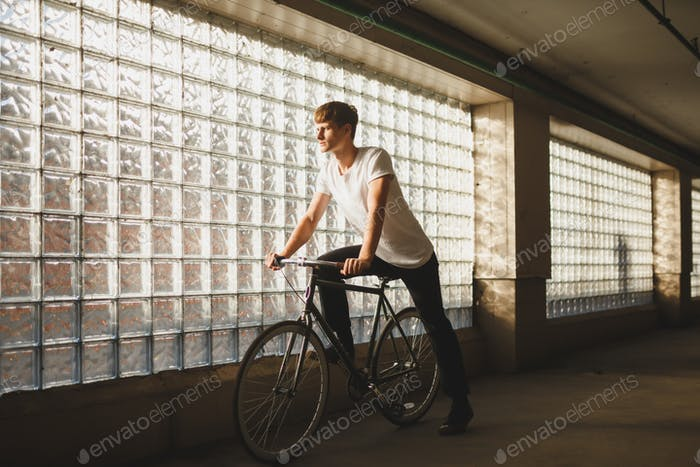 Young thoughtful man in white t-shirt standing with bicycle with glass wall on background