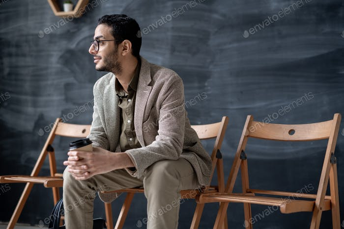 Young elegant businessman with glass of coffee sitting on chair in modern cafe