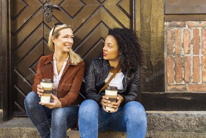Zwei Frauen sitzen auf Treppen und reden