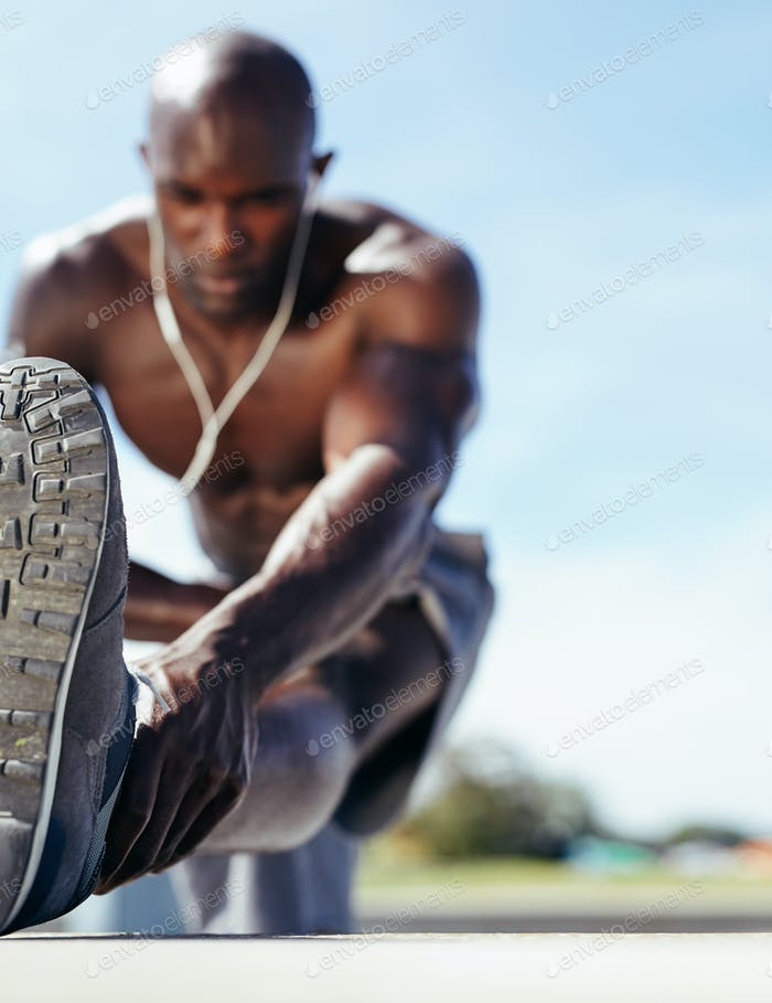 Male athlete stretching his leg muscles