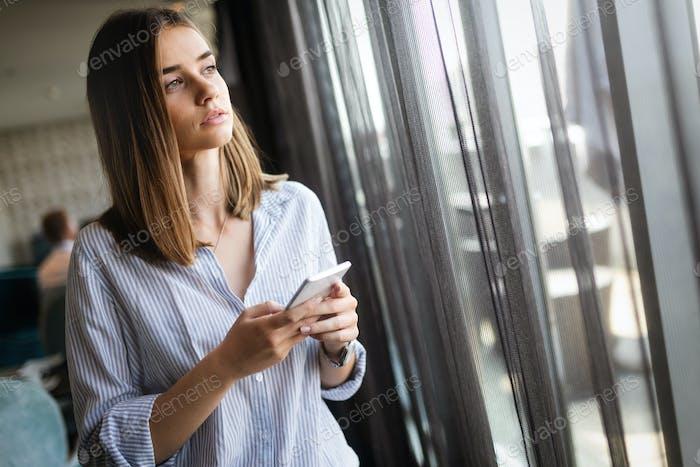 Konzentrierte Frau denkt mit Telefon in den Händen