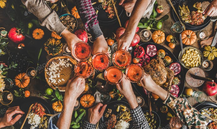 Family celebrating Thanksgiving day with Autumn food and rose wine