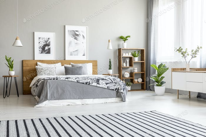 Striped carpet in spacious bright bedroom interior with posters