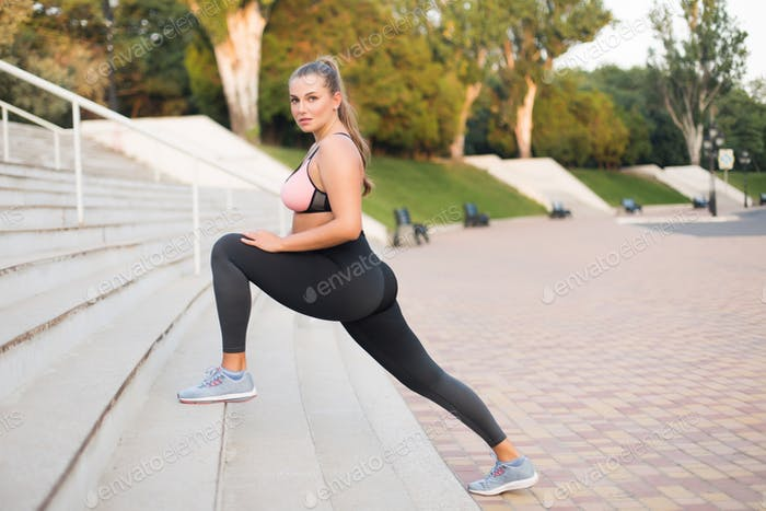 Young attractive plus size woman in sport top and leggings thoug