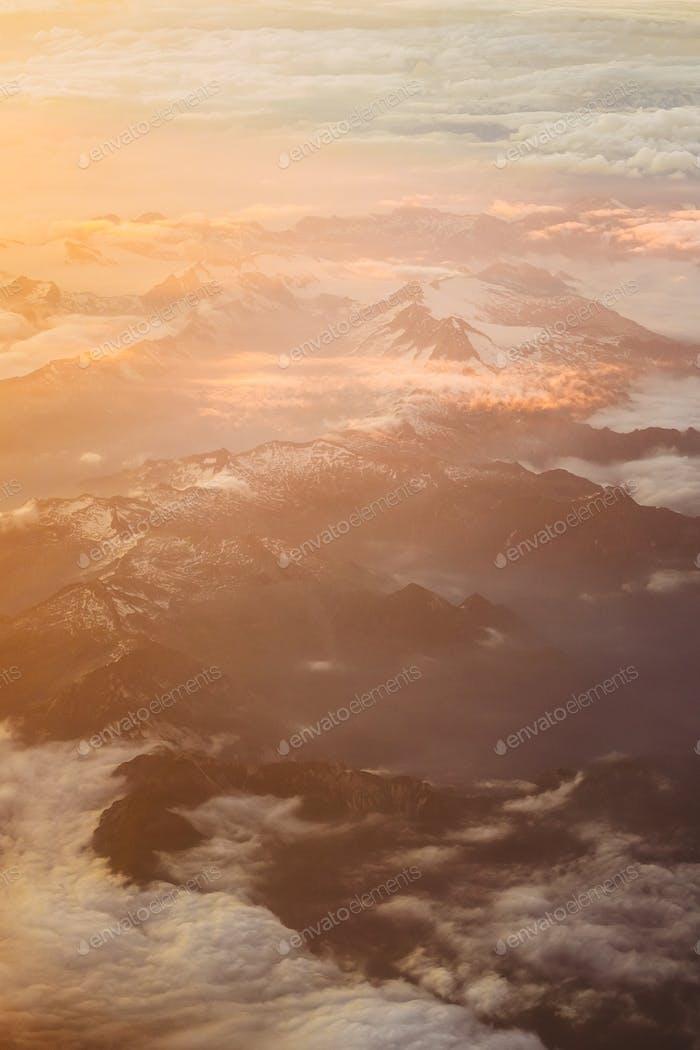Sonnenuntergang über den Bergen von der Höhe des Flugzeugs. Hellorange, Ye