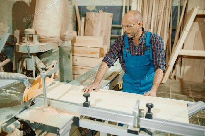 Zimmermann schneidet Holzbrett auf Kreissäge