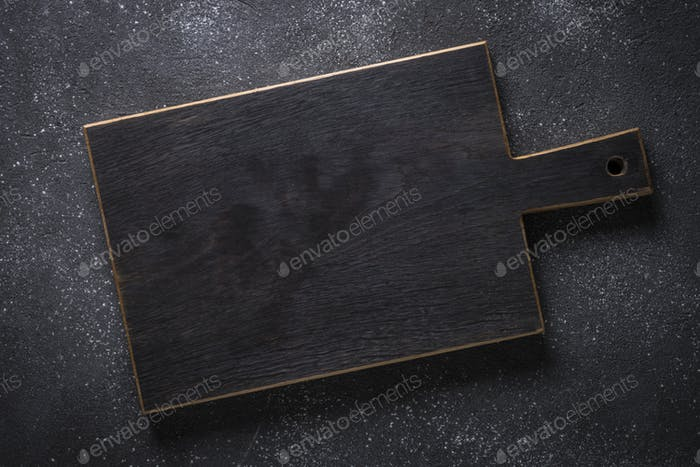 Black wooden cutting board on black stone table