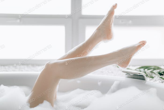 Pretty young woman relax in bath with foam