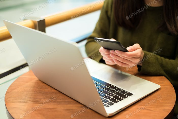 Woman use of mobile phone with her computer at coffee shop