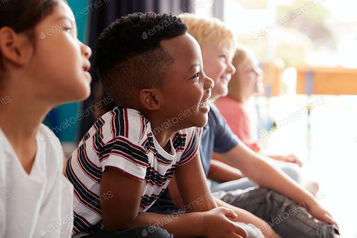 Group Of Elementary School Pupils Sitting On Floor Listening To Teacher