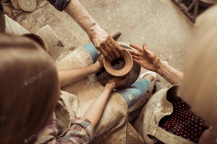 Overhead-Ansicht des kleinen Mädchens, die Keramik auf dem Rad mit Hilfe der Großeltern in der Werkstatt