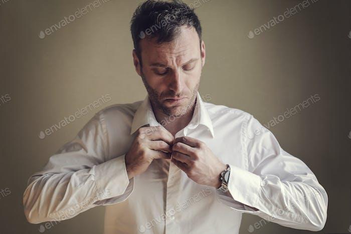Man fastening his shirt