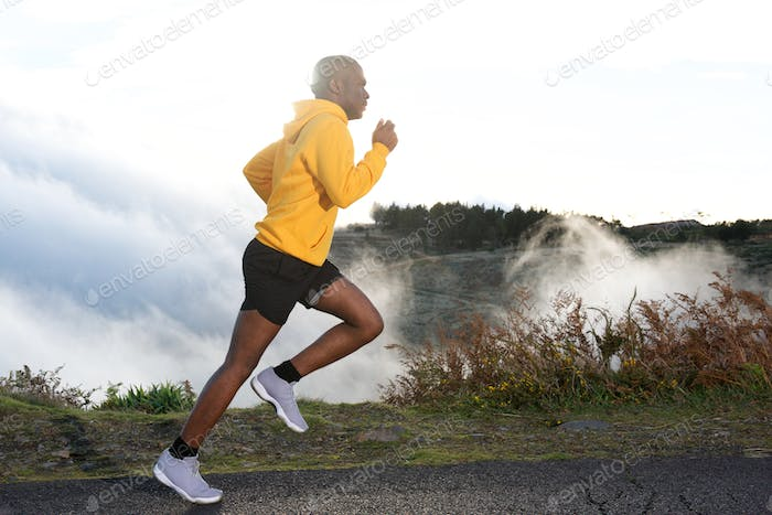 Full body side of young black man road running in nature