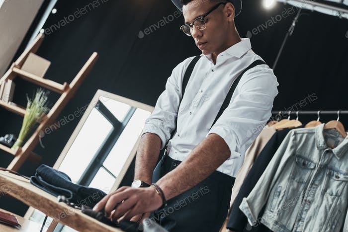 Concentrated on work. Serious young man arranging menswear while standing in the showroom