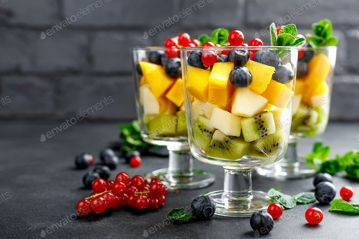 Fresh salad with fruits and berries in glass