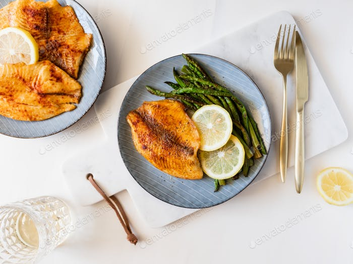 Roasted tilapia fish with asparagus on a ceramic plate