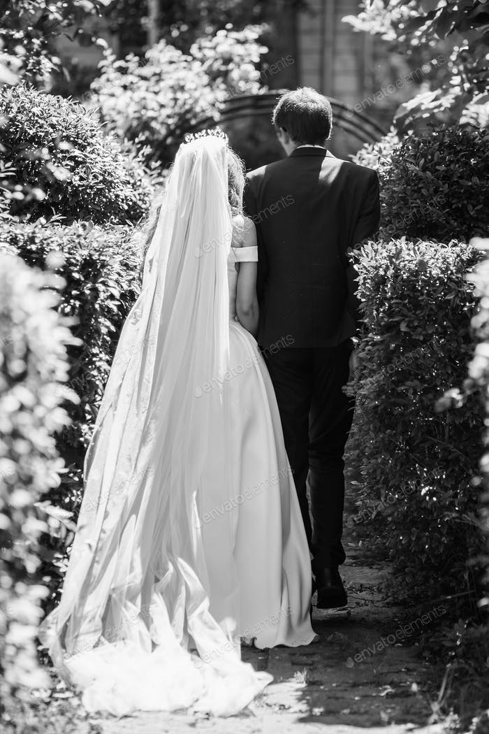 Bride in silk dress and groom in suit hugging in sunny garden on wedding day