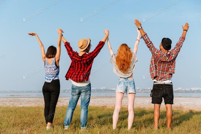 Rückansicht von Freunden stehend und halten erhobenen Händen im Freien