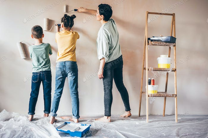 Happy mother, daughter and son painting wall .