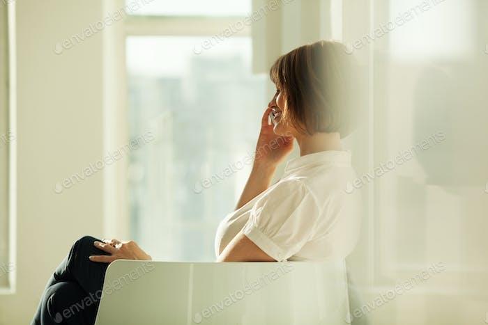 Vista lateral de la mujer de negocios sonriente hablando por teléfono