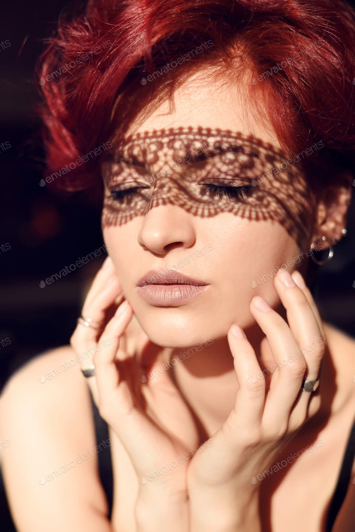 Portrait of beautiful woman with shadows of openwork on sensual