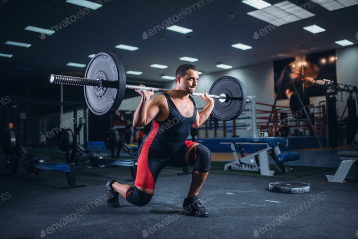 Weight lifter doing squats with a barbell in gym