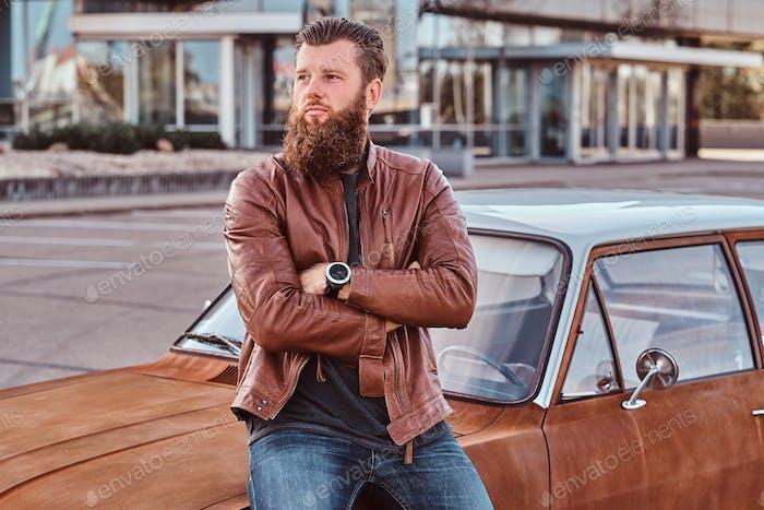Бородатый мужчина, одетый в коричневую кожаную куртку, опираясь на настроенный ретро автомобиль на городской парковке.