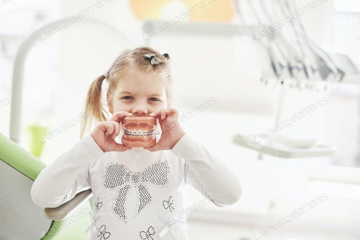 Ein kleines Mädchen in der Zahnarztpraxis hält ein Modell des Kiefers und Posen