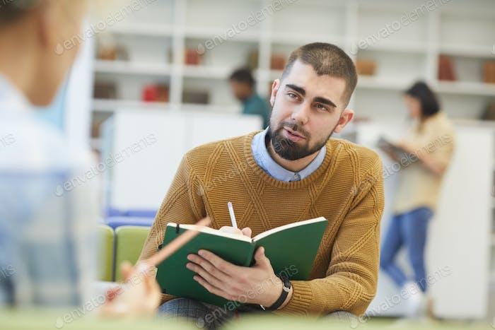 Junger Mann Studieren in Bibliothek