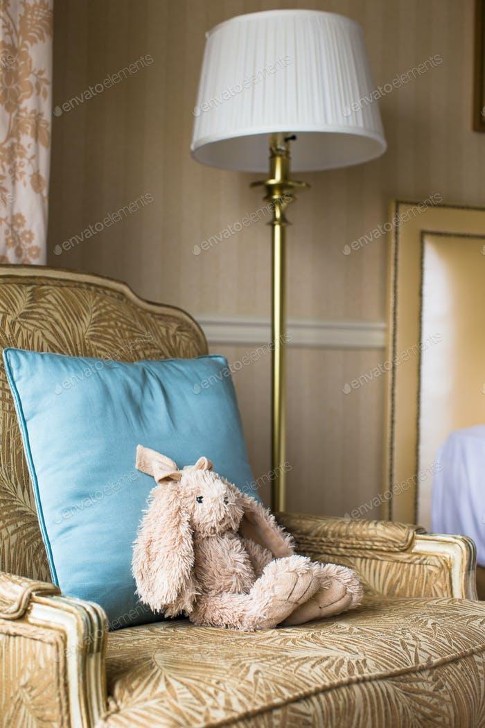 Soft plush toy bunny on a chair in a hotel room