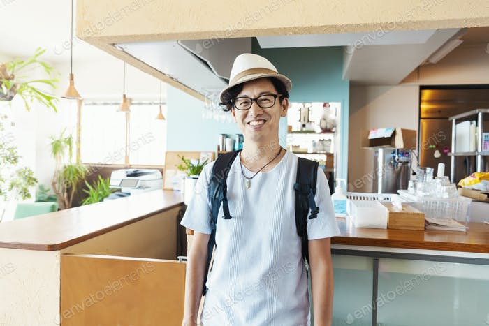 Male Japanese professional standing in a co-working space, smiling at camera.