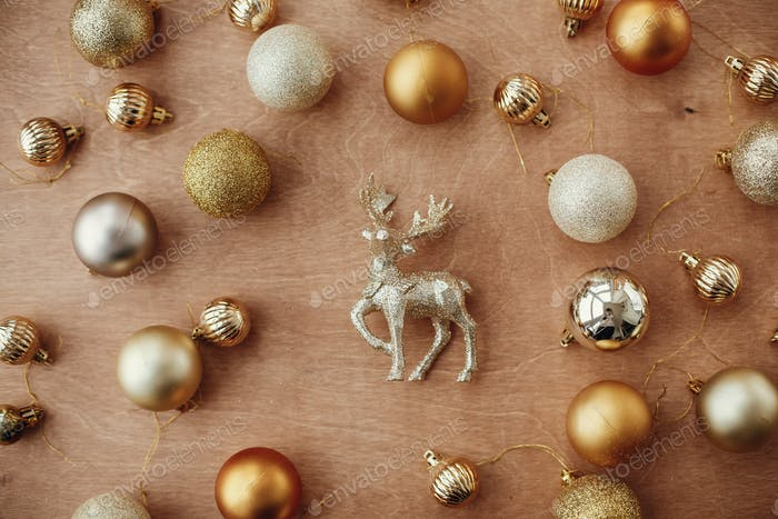 Christmas golden glitter reindeer and shiny baubles and balls on rustic background, flat lay