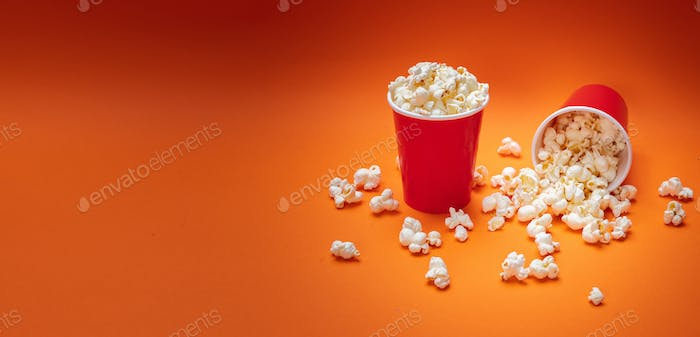 Pop corn scattered on orange color background, top view
