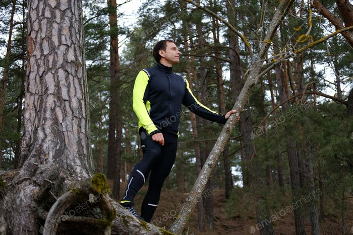 A man posing in the forest.