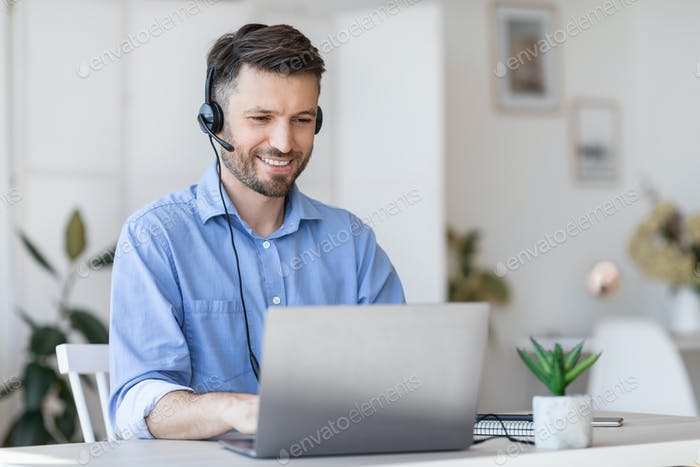 Call center operator at work. Male manager wearing headset and using laptop