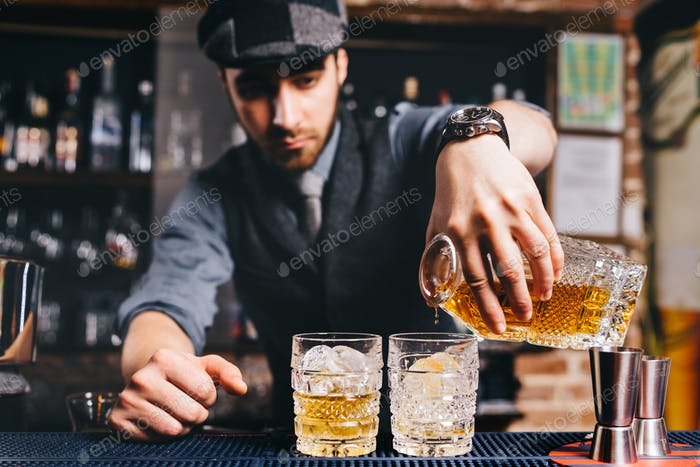 Barman pouring whiskey cocktail in crystal glasses