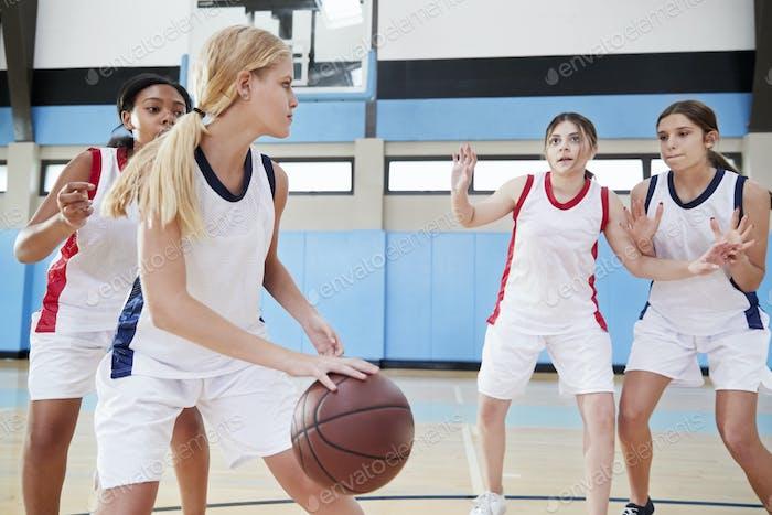 Female High School Basketball Team Dribbling Ball On Court